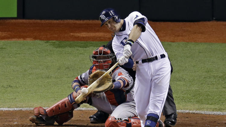 Tampa Bay Rays third baseman Evan Longoria, right, hits a three-run home run as Boston Red Sox catcher Jarrod Saltalamacchia watches in the fifth inning during Game 3 of an American League baseball division series in St. Petersburg, Fla., Monday, Oct. 7, 2013. (AP Photo/John Raoux)