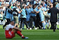 Manchester City&#39;s players and supporters celebrate on the pitch after their 3-2 victory over Queens Park Rangers. Sergio Aguero&#39;s last minute goal sealed the most enthralling title duel in years