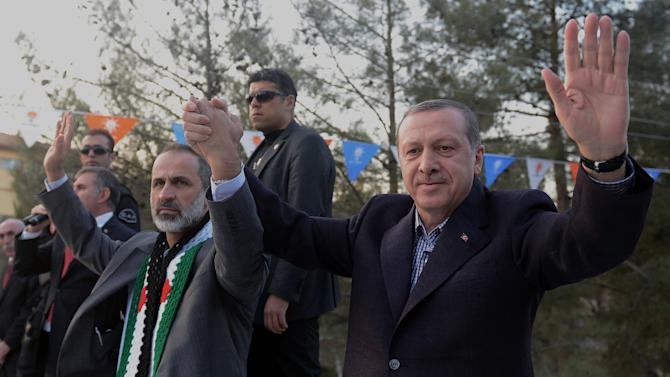In this photo provided by Turkish Prime Minister's Press Service, Turkish Prime Minister Recep Tayyip Erdogan, right, flanked by the Syrian opposition coalition leader Mouaz al-Khatib, waves to people as he addresses residents of a Turkish village near the Syrian border, in Sanliurfa, Turkey, Sunday, Dec. 30, 2012. Erdogan repeated a call on Syrian President Bashar Assad to step down. (AP Photo/Kayhan Ozer)