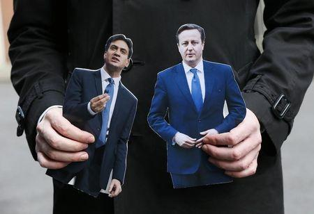 A journalist standing in Downing Street holds cardboard cutouts of Britain's Prime Minister David Cameron and Ed Miliband, the leader of the opposition Labour Party, in central London