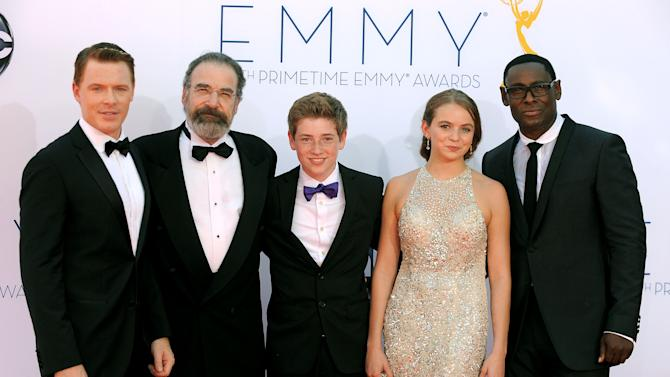 """The cast of """"Homeland"""", from left, Diego Klattenhoff, Mandy Patinkin, Jackson Pace, Morgan Saylor and David Harewood, arrives at the 64th Primetime Emmy Awards at the Nokia Theatre on Sunday, Sept. 23, 2012, in Los Angeles.  (Photo by Jordan Strauss/Invision/AP)"""