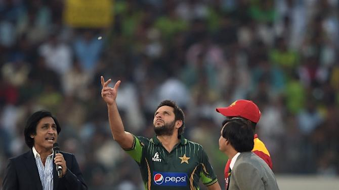 Pakistan's captain Shahid Afridi (C) tosses a coin as he stands next to his Zimbabwe counterpart Elton Chigumbura (red cap) before the start of the first International T20 match at the Gaddafi Cricket Stadium in Lahore