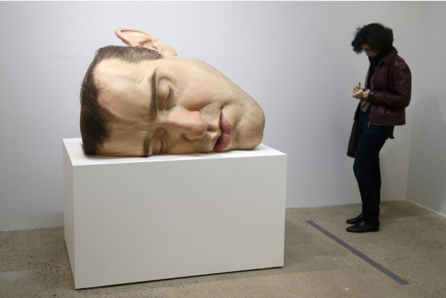 "A visitor looks at a sculpture entitled ""Mask II"" by artist Ron Mueck during his exhibition at the Fondation Cartier pour l'art contemporain in Paris"