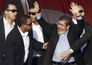 Egypt's Islamist President-elect Mohamed Mursi waves to his supporters while surrounded by his body guards in Cairo's Tahrir Square, June 29, 2012. Mursi took an informal oath of office on Friday before tens of thousands of supporters in Cairo's Tahrir Square, in a slap at the generals trying to limit his power. REUTERS/Amr  Abdallah Dalsh (EGYPT - Tags: POLITICS CIVIL UNREST)