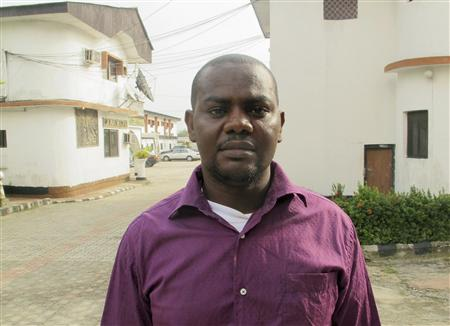 Okene poses for photograph after an interview with Reuters outside an hotel in Nigeria's oil city of Warri