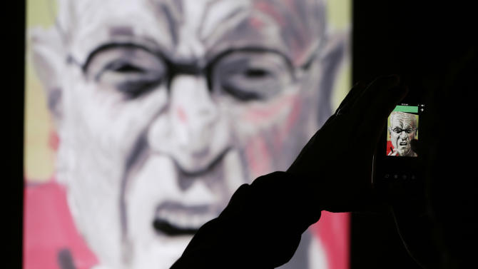 In this photo taken Thursday, Oct. 24, 2013, a man records how a painting made by David Hockney using an iPad takes shape at an exhibit in San Francisco. A sweeping new exhibit of Hockney's work, including about 150 iPad images, has opened in the deYoung Museum in Golden Gate Park, just a short trip for Silicon Valley techies who created both the hardware and software for this magnificent reinvention of fingerpainting. (AP Photo/Eric Risberg)