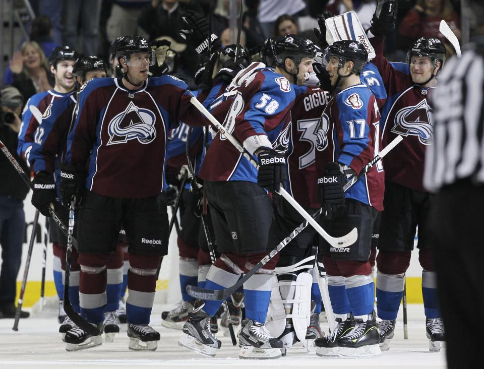 Colorado Avalanche left wing Patrick Bordeleau, front left, congratulates teammate Aaron Palushaj as they join teammates to celebrate the Avalanche's 6-2 victory over the Chicago Blackhawks in an NHL hockey game in Denver on Friday, March 8, 2013. Chicago's loss was its first in regulation this season. (AP Photo/David Zalubowski)