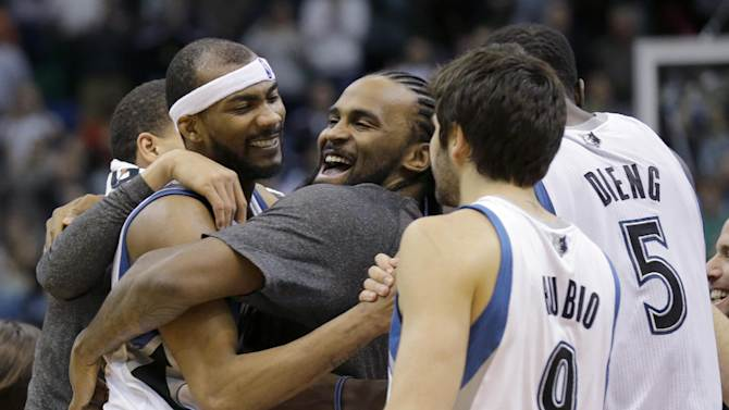 Minnesota Timberwolves forward Corey Brewer, left,  celebrates with teammates Ronny Turiaf, center, of France; Ricky Rubio (9), of Spain; and Gorgui Dieng (5) after the Timberwolves defeated the Houston Rockets 112-110 in an NBA basketball game in Minneapolis, Friday, April 11, 2014
