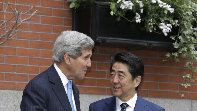 Secretary of State JohnKerry, left, greets Japanese Prime Minister Shinzo Abe in front of Kerry's residence in the Beacon Hill neighborhood of Boston, Sunday, April 26, 2015. Abe arrived in the U.S. Sunday for a weeklong visit. (AP Photo/Steven Senne)