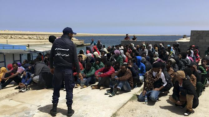 Coast guard stands over illegal migrants who attempted to sail to Europe, on the shore after the migrants' boat was intercepted at sea by the Libyan coast guard, at Khoms, Libya