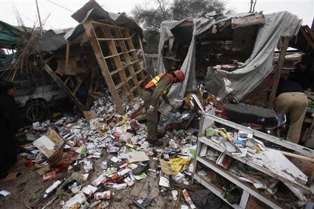 A rescue worker collects evidence at the site of a bomb blast on outskirts of Peshawar