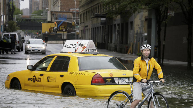 """FILE - In this Aug. 28, 2011 file photo, a bicyclist makes his way past a stranded taxi on a flooded New York City street as Tropical Storm Irene passes through the city. From Cape Hatteras, N.C., to just north of Boston, sea levels are rising much faster than they are around the globe, putting one of the world's most costly coasts in danger of flooding, according to a new study published Sunday, June 24, 2012, in the journal Nature Climate Change. By the year 2100, scientists and computer models estimate that sea levels globally could rise as much as 3.3 feet. The accelerated rate along the East Coast could add about another 8 to 11 inches, Asbury Sallenger Jr., an oceanographer for the USGS said. """"Where that kind of thing becomes important is during a storm,"""" Sallenger said. That's when it can damage buildings and erode coastlines. (AP Photo/Peter Morgan, File)"""