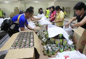 Soldiers and volunteers prepare relief goods, to be …