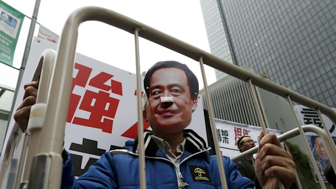 File photo of demonstrator wearing a mask depicting Causeway Bay Books shareholder Lee Bo during a protest in Hong Kong