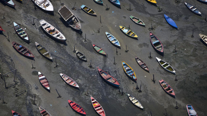 Small boats sit on the shore of Guanabara Bay in the suburb of Sao Goncalo, across the bay from Rio de Janeiro, Brazil, Tuesday, Nov. 19, 2013. The bay was home to a thriving artisanal fishing industry and popular palm-lined beaches as recently as the late-1970s, but has become a watery dump for waste from shipyards and two commercial ports. Rio de Janeiro will host the 2016 Olympic Games. (AP Photo/Felipe Dana)