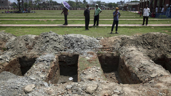 Graves at a cemetery where unclaimed bodies are buried, are prepared for a mass burial for victims of the garment factory building that collapsed, Wednesday, May 1, 2013, in Dhaka, Bangladesh. Several hundred people attended a mass funeral in the Dhaka suburb for 18 unidentified workers who died in the building collapse last week in the country's worst industrial disaster, killing at least 402 people and injuring 2,500.   (AP Photo/Wong Maye-E)