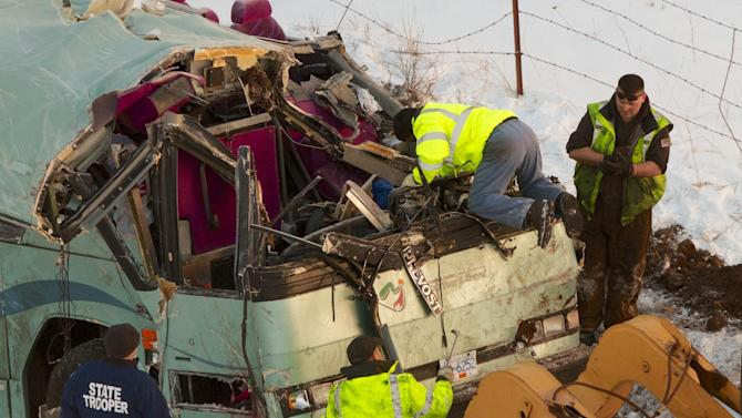 Workmen move the bus which plummeted 200 feet down an embankment in rural Eastern Oregon Sunday, killing nine and sending multiple to hospitals, Monday, Dec. 31, 2012. Survivors of the bus crash said Monday some passengers were thrown from the tour bus through broken windows after the vehicle skidded out of control, smashed through a guardrail and went down. (AP Photo/The Oregonian, Randy L. Rasmussen)