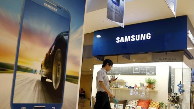 Man using his mobile phone walks past a Samsung Electronics shop in the company's main office building in central Seou