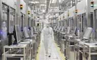 An employee of Japan&#39;s microprocessor maker Renesas Electronics works at the company&#39;s Naka wafer fabrication factory in Hitachinaka, Ibaraki prefecture on June 10, 2011. Struggling Japanese chipmaker Renesas Electronics on Friday posted a $1.73 billion net loss in the nine months to December, and chopped its annual earnings forecast by 17 percent