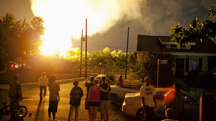 FILE - In this July 11, 2012 file photo, people watch flames shoot up from a freight train that derailed and some cars burst into flames in Columbus Ohio. The accident prompted the evacuation of a mile-wide area as firefighters and hazardous materials crews monitored the blaze. For two decades, one of the nation's most common types of rail tankers, known as a DOT-111s, have been allowed to haul hazardous liquids from coast to coast even though transportation officials were aware of a dangerous design flaw that almost guarantees the car will tear open in an accident. The rail and chemical industries have committed to a safer design for new tankers, but they do not want to modify tens of thousands of existing cars. That's despite a spike in the number of accidents. (AP Photo/Andrew Spear, File)
