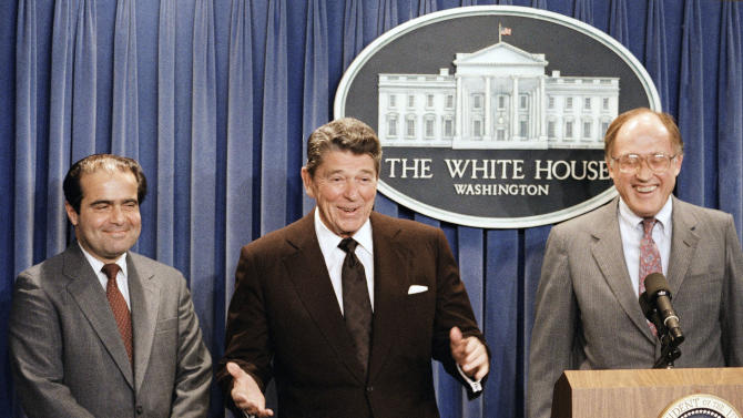 FILE - In this June 17, 1986 file photo, President Ronald Reagan speaks at a news briefing at the White House in Washington, where he announced the nomination of Antonin Scalia, left, to the Supreme Court as a result of Chief Justice Warren E. Burger's resignation. William Rehnquist is at right. On Saturday, Feb. 13, 2016, the U.S. Marshals Service confirmed that Justice Scalia has died at the age of 79. (AP Photo/Ron Edmonds)