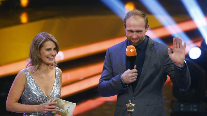 """German discus thrower Harting waves next to TV host Mueller-Hohenstein after being awarded Germany's Athlete Of The Year 2014 during the """"Sportsmen Of The Year"""" gala in Baden Baden"""