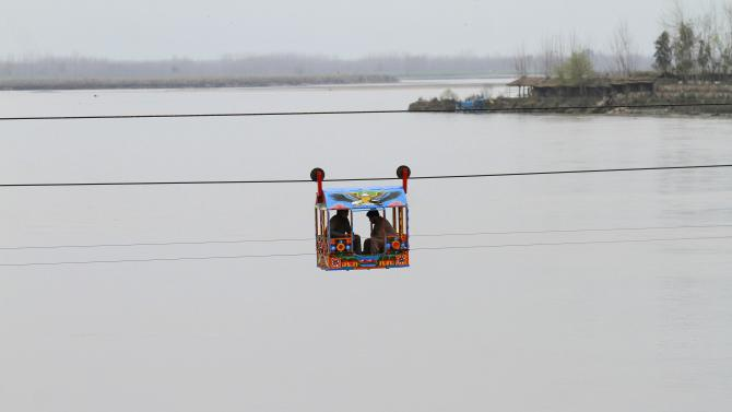 Men sit in a makeshift chairlift to cross a river in Charsadda