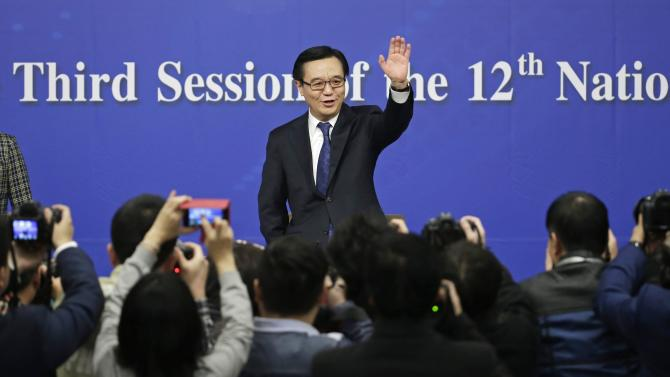 China's Minister of Commerce Gao Hucheng waves to the media in Beijing