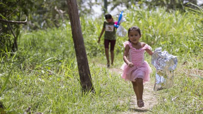 A child runs with her gift after receiving it from the Amigos do Papai Noel at the community Sao Jose in Careiro da Varzea