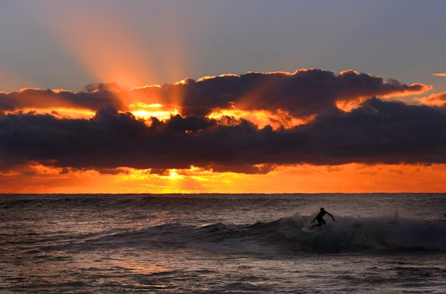 SYDNEY, AUSTRALIA - APRIL 05:  A surfer rides a wave at dawn on Bronte Beach on April 05, 2013 in Sydney, Australia.  (Photo by Michael Regan/Getty Images)