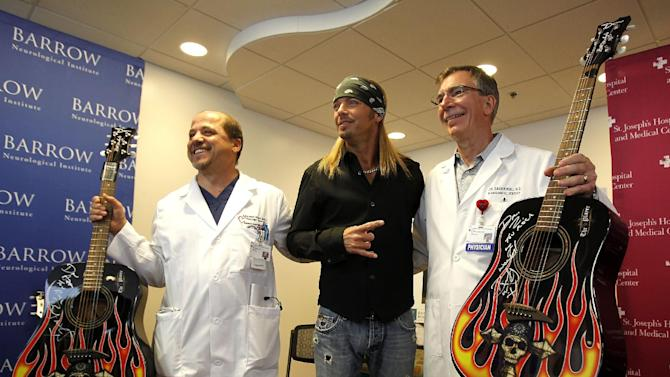 Poison frontman Bret Michaels, middle, poses with two of his doctors, Mansour Assar, a cardiovascular doctor at St. Joseph's Hospital, and Joseph Zabramski, a neurosurgeon at St. Joseph's Hospital, after giving the doctors one of his signature guitars each, and after Michaels talked about the designs for a music room he will be funding and decorating at St. Joseph's Hospital and Medical Center Barrow Neurological wing Thursday, Oct. 27, 2011, in Phoenix.  Michaels is a former patient at the Barrow Neurological center, after suffering a type of life-threatening stroke in 2010. (AP Photo/Ross D. Franklin)