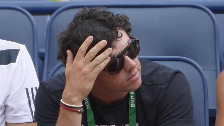 PGA golfer Rory McIlroy, of Northern Ireland, watches as his fiance, Caroline Wozniacki, of Denmark, plays a fourth round match against Jelena Jankovic, of Serbia, at the BNP Paribas Open tennis tournament, Tuesday, March 11, 2014, in Indian Wells, Calif. (AP Photo/Mark J. Terrill)