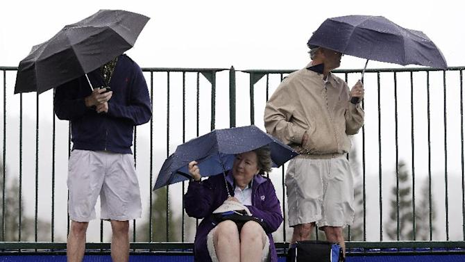 Fans huddle under umbrellas in the rain and wind as they wait for players to tee off in the first round at the Tournament of Champions golf tournament on Friday, Jan. 4, 2013, in Kapalua, Hawaii. (AP Photo/Elaine Thompson)