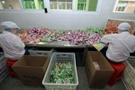 File photo of Chinese workers packing candy at a factory in Jinjiang, southeast China's Fujian province. China is facing a loss of momentum in its economy, with year-on-year growth slowing to 7.6 percent in the second quarter