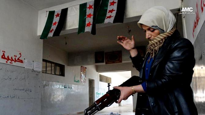 This Tuesday, May 14, 2013 citizen journalism image provided by Aleppo Media Center AMC which has been authenticated based on its contents and other AP reporting, shows the mother of a Syrian rebel cleaning a rifle, in Aleppo, Syria. Activists say Syrian rebels have detonated two car bombs outside the main prison in the northern city of Aleppo and are trying to storm the facility, where hundreds of regime opponents are believed to be held. (AP Photo/Aleppo Media Center AMC)