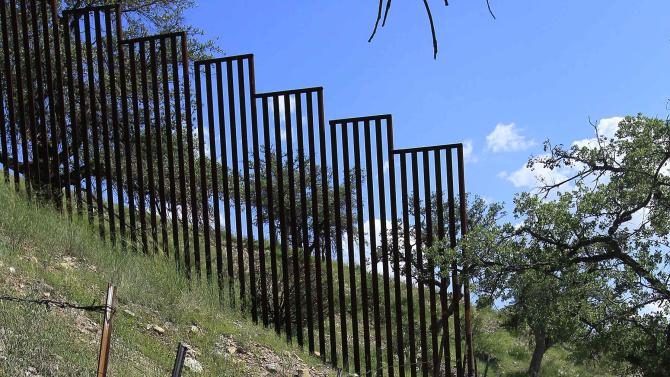In this Friday, Aug. 10, 2012 photo, a small barbed-wire fence begins where the more imposing fence ends on the property of rancher Dan Bell, along the border between the United States and Mexico, in Nogales, Ariz. When Bell drives through his property, he speaks of the hurdles that the Border Patrol faces in his rolling green hills of oak and mesquite trees: The hours it takes to drive to some places, the wilderness areas that are generally off-limits to motorized vehicles, and the environmental reviews required to extend a dirt road. (AP Photo/Ross D. Franklin)