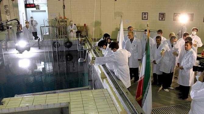 FILE- In this Feb. 15, 2012, file photo, provided by the Iranian President's Office, Iranian President Mahmoud Ahmadinejad, right, is escorted by technicians during a tour of Tehran's research reactor center in northern Tehran, Iran. Gholamreza Mesbahi Moghadam, a prominent Iranian lawmaker, said Friday, April 6, 2012, in an interview with the parliament's news website, icana.ir, that Iran can easily produce the highly enriched uranium that is used to build atomic bombs but it is not Tehran's policy to go that route. His views do not represent the Iranian government's policy. (AP Photo/Iranian President's Office, File)