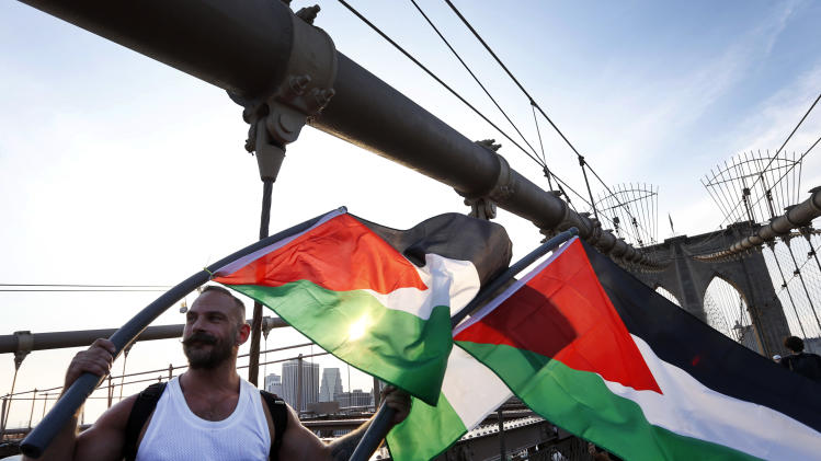 Demonstrators march across the Brooklyn Bridge during a pro-Palestinian rally, Wednesday, Aug. 20, 2014, in New York. (AP Photo/Jason DeCrow)