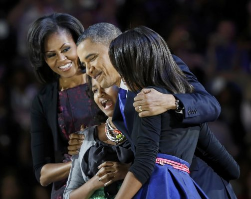President Obama hugs daughters at victory rally in Chicago