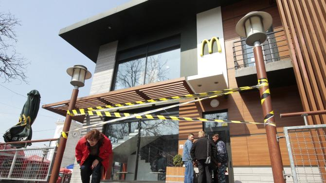 A woman makes her way under a barrier tape outside a McDonald's restaurant, which was earlier closed for clients, in the Crimean city of Simferopol