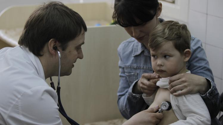 In this Monday, April 23, 2013 photo pediatrician Fyodor Lapiy examines a child before administering him a combined vaccine against diphtheria, whopping cough and tetanus in Children's Hospital No. 1 in Kiev,Ukraine. Only about one-half of Ukraine's children are fully immunized against vaccine-preventable communicable diseases in line with local health regulations, compared to over 90 percent in Western Europe, according to UNICEF, the United Nations children's agency. Such a low immunization rate has already led to a major outbreak of measles and a risk of an outbreak of polio, a highly dangerous disease which may cause paralysis and which has been unseen in Ukraine for more than a decade, UNICEF and the World Health Organization said ahead of the current World Immunization week. (AP Photo/Sergei Chuzavkov)
