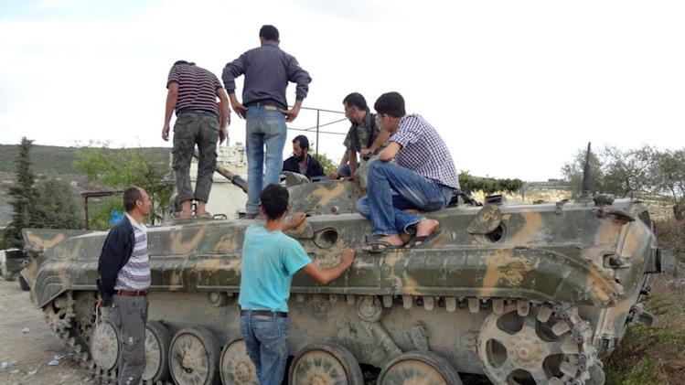 In this Sunday October 7, 2012 citizen journalism image provided by Edlib News Network, ENN, which has been authenticated based on its contents and other AP reporting, Free Syrian Army fighters check a tank that was captured from the Syrian Army in Khirbet al-Jouz, in the northern province of Idlib, Syria. The Turkish state-run Anadolu news agency said Sunday that the rebels had regained full control of Khirbet al-Jouz. (AP Photo/Edlib News Network ENN)
