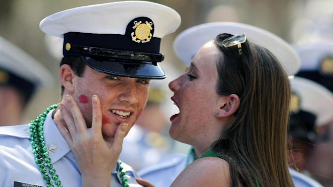U.S Coast Guard Petty Officer 3rd Class Tanner Marshall is kissed by a woman during a St. Patrick's Day parade, Saturday, March, 16, 2013, in Savannah, Ga. St. (AP Photo/Stephen Morton)