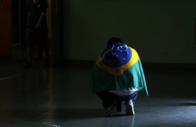 A volleyball fan wearing Brazil's flag kneels by a doorway before the start of a women's gold medal volleyball match between the United States and Brazil at the 2012 Summer Olympics, Saturday, Aug. 11