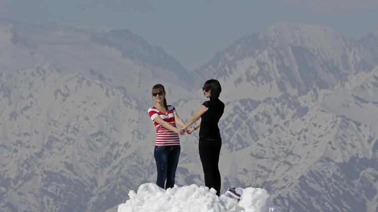 "Women pose for pictures on top of the ""Peak Rosa"" of Rosa Khutor during a warm and sunny day at the 2014 Sochi Paralympic Winter Games"