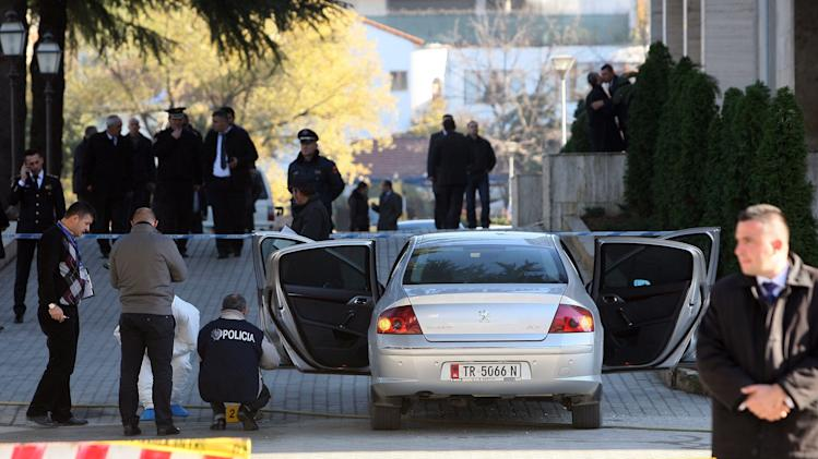 Bomb squad experts inspect a car at the entrance of Albania's main government building in Tirana