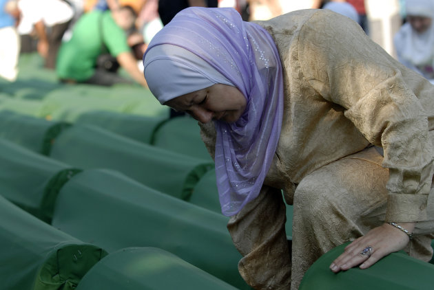 Bosnian Muslim woman weeps while she touches a coffin of her relative among the over five-hundred coffins displayed at the Potocari memorial cemetery near Srebrenica, some 160 kilometers east of Sarajevo, Bosnia, Wednesday, July 11, 2012. Thousands gathered in the cemetery for the mass burial of 520 bodies, marking 17th anniversary of the Srebrenica massacre. (AP Photo/Sulejman Omerbasic)