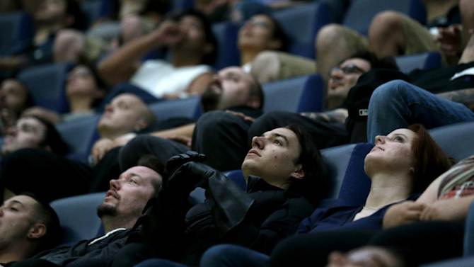 """FILE - This July 20, 2012 file photo shows a wide awake crowd watching the premier of """"The Dark Knight Rises"""" inside the Liberty Science Center IMAX theater in Jersey City, N.J. Movie napping is a precarious affair and almost certainly as old as cinema itself. It strikes the overtired and the well-rested, film nuts and occasional theatergoers. Any which way, cinematic snoozing seems near epidemic proportions this awards season with buzz plus ZZZs for """"Lincoln,"""" the 157-minute sung """"Les Miserables,"""" the 169-minute """"The Hobbit: An Unexpected Journey"""" and others cited as good for a snore.  (AP Photo/Julio Cortez, file)"""
