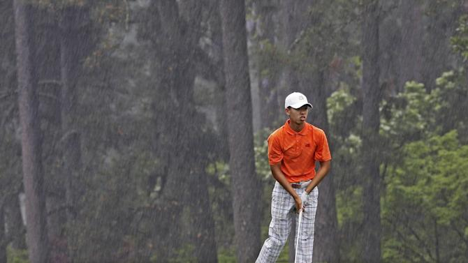 Amateur Guan Tianlang, of China, watches his ball after hitting in the rain on the eighth fairway during the second round of the Masters golf tournament Friday, April 12, 2013, in Augusta, Ga. (AP Photo/David J. Phillip)