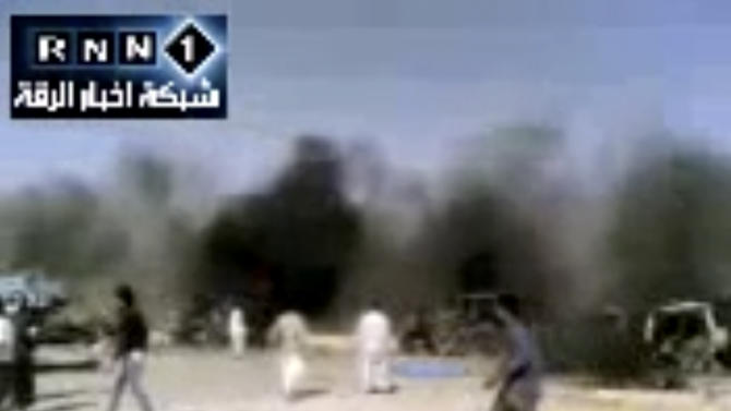 In this image taken from video obtained Thursday, Sept. 20, 2012 from the Ugarit News, which has been authenticated based on its contents and other AP reporting, people are seen after an airstrike on a gas station in Raqqa, Syria. Syrian opposition activists said a regime airstrike hit a gas station in the north of the country Thursday, setting off an explosion that killed and wounded dozens of people. (AP Photo/Ugarit News via AP video)